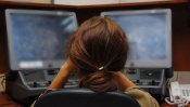 Une guetteuse derrière ses écrans d'ordinateur