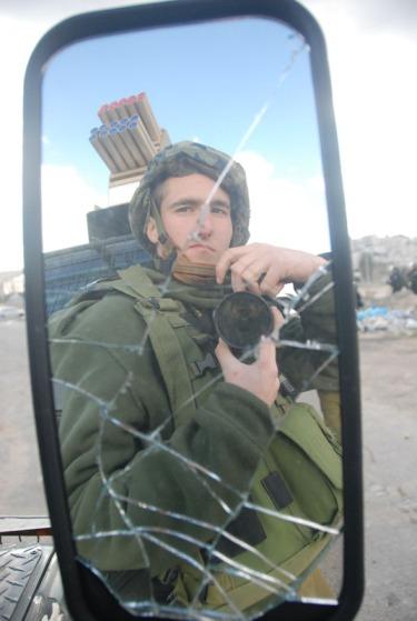 Gil K., dans le rétroviseur cassé par une pierre des émeutiers d'un camion militaire